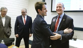 In this Tuesday, May 14, 2019 photo, Dan Bishop, right, gets a hug from his son Jack Bishop after he addressed supporters as voting totals came in, in Charlotte, N.C.  Bishop topped nine other Republican candidates seeking the 9th Congressional District nomination on Tuesday, winning almost half of the ballots cast in an extremely low turnout election that drew less than 10% of the eligible voters. He will face Democrat Dan McCready, as well as Libertarian and Green candidates, on Sept. 10.  (John D. Simmons/The Charlotte Observer via AP)