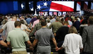 FILE - In this June 12, 2018 file photo, people pray for America at the 2018 annual meeting of the Southern Baptist Convention at the Kay Bailey Hutchison Dallas Convention Center in Dallas.  The nation's largest Protestant denomination is reporting its twelfth year of declining memberships. On Thursday, May 23, 2019, the Southern Baptist Convention reported total membership for 2018 at 14.8 million, down about 192,000 from the previous year. (Vernon Bryant/The Dallas Morning News via AP, File)