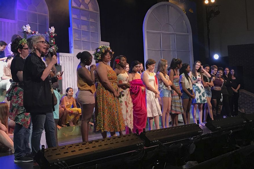 This image released by Madeline Michel shows Monticello Drama director Michel, foreground left, on stage with Monticello High School students in Charlottesville, Va. Michel will be the recipient of the  2019 Excellence in Theatre Education Award on June 9 at the Tony Awards in New York City.  (Madeline Michel via AP)