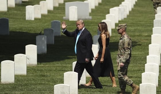 Then-President Donald Trump and first lady Melania Trump visit Arlington National Cemetery for the annual Flags In ceremony ahead of Memorial Day Thursday, May 23, 2019, in Arlington, Va. (AP Photo/Andrew Harnik) ** FILE **