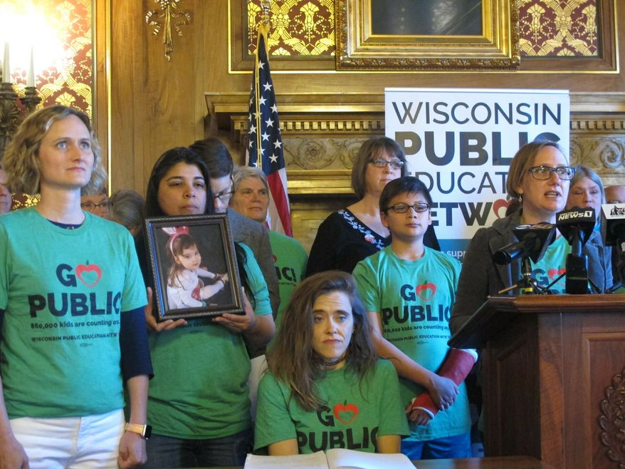 Wisconsin Public Education Network leader Heather DuBois Bourenane, right, says a Republican K-12 education plan that increases funding by $500 million over two years isn't enough to meet needs of districts, on Thursday, May 23, 2019, in Madison, Wis. The Republican funding plan is $900 million less than what Gov. Tony Evers proposed. (AP Photo/Scott Bauer)