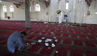 An Afghan Journalist take a photo inside a mosque after a bomb explosion during Friday prayer on the outskirts of Kabul, Afghanistan, Friday, May 24, 2019. According to Kabul police chief's spokesman, Basir Mujahid, the bomb was concealed in the microphone used to deliver the sermon. The prayer leader, Maulvi Samiullah Rayan, was the intended target, the spokesman added. (AP Photo/Rahmat Gul)