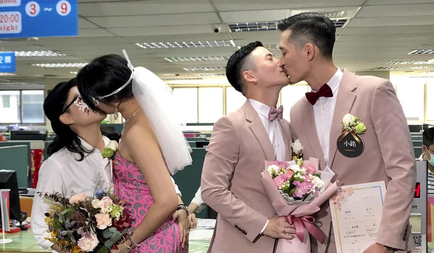 Two same-sex couples seal their legal marriage with a kiss at the registration office in Xingyi District in Taipei, Taiwan, Friday, May 24, 2019. Hundreds of same-sex couples in Taiwan are rushing to the household registration office on the first day that a landmark decision to legalize same-sex marriage has taken effect. (AP Photo/Johnson Lai)