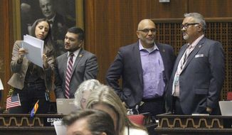 Four Democratic members of the Arizona House, from left, Athena Salman, Andres Cano, Diego Espinoza and Lorenzo Sierra confer on the House floor as a state budget plan awaits action, Thursday, May 23, 2019 in Phoenix. The Legislature moved in fits and starts as majority Republicans tried to round up the votes they need to pass the $11.8 billion spending plan without Democratic support. (AP Photo/Bob Christie)