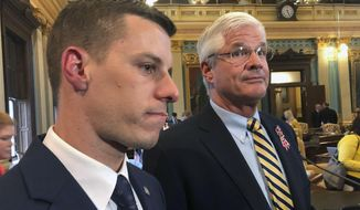 Republican House Speaker Lee Chatfield, left, and Republican Senate Majority Leader Mike Shirkey speak with reporters following the Michigan Legislature's approval of auto insurance legislation on Friday, May 24, 2019, at the Capitol in Lansing, Mich. Democratic Gov. Gretchen Whitmer is expected to sign the bill. (AP Photo/David Eggert)