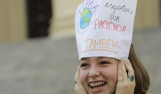 """A student holds a sign up to her forehead with a message that reads in Portuguese: """"Earth has lost its patience, us too"""", during a protest against President Jair Bolsonaro's environmental policies, in front of the state legislature in Rio de Janeiro, Brazil, Friday, May 24, 2019. A small group of students gathered outside the state legislature to deliver a letter dated from the future in which they lamented Brazil's loss of coastline, rainforests and species. (AP Photo/Silvia Izquierdo)"""