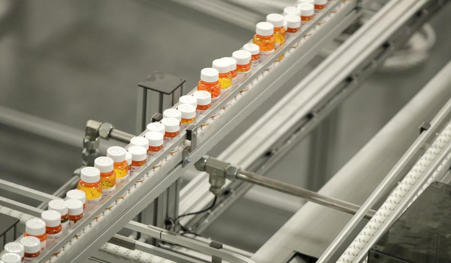 FILE- In this July 10, 2018, file photo bottles of medicine ride on a belt at a mail-in pharmacy warehouse in Florence, N.J. The highest pay packages go to CEOs at health care companies. For the third time in four years, chief executives in the health care field led the S&P 500 in terms of total compensation. (AP Photo/Julio Cortez, File)