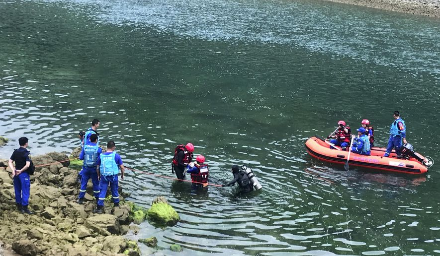 In this photo released by China's Xinhua News Agency, rescuers search a river after a boat capsized near Banrao village in southwestern China's Guizhou province, Friday, May 24, 2019. Chinese state media reported that a number of people died and others are missing after a boat capsized in southwestern China on Thursday evening. (Shi Qiangui/Xinhua via AP)