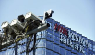 """In this Wednesday, May 22, 2019, photo, surveillance cameras are seen outside the headquarters of Chinese security technology company Hikvision in Hangzhou in eastern China's Zhejiang province. Stepping up a propaganda offensive against Washington, China's state media on Friday accused the U.S. of seeking to """"colonize global business"""" by targeting telecom equipment giant Huawei and other Chinese companies. (Chinatopix via AP)"""