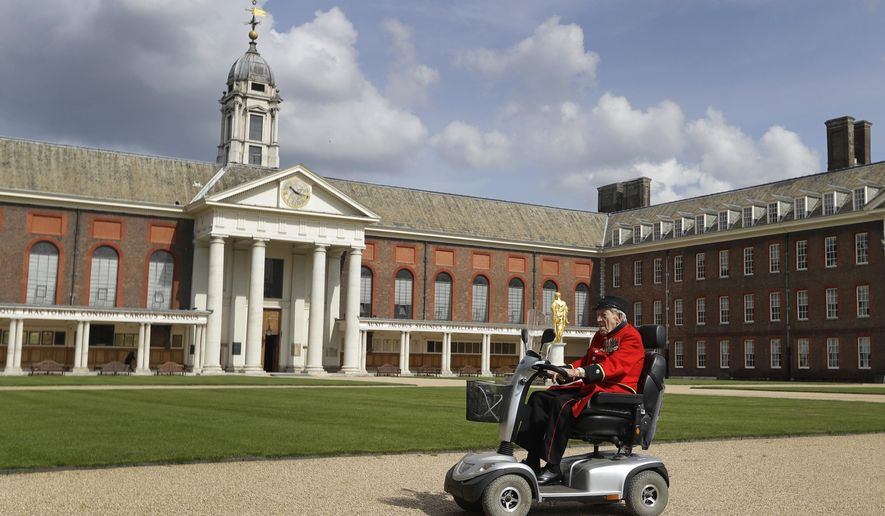In this May 7, 2019, photo, Chelsea Pensioner and D-Day veteran George Skipper arrives on his mobility scooter for an interview with The Associated Press at the Royal Hospital in Chelsea, London. With the number of survivors dwindling every year, men like Skipper are on a mission to share their experiences. (AP Photo/Kirsty Wigglesworth)