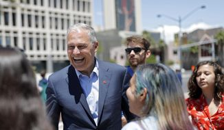 Democratic presidential candidate Washington Gov. Jay Inslee, center, meets with students at a climate change rally Friday, May 24, 2019, in Las Vegas. (AP Photo/John Locher)