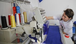 In this picture taken Tuesday, May 21, 2019, Valentina Radu works on an automated sewing machine in Luncavita, Romania. Radu also worked in Italy, but when her husband lost his job there, they struggled to pay the rent and decided to come home where they used European Union funds to buy a small farm and she further opened a tailor's shop. (AP Photo/Vadim Ghirda)