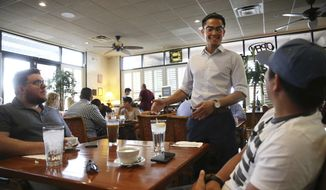 ADVANCE FOR USE IN WEEKEND EDITIONS, SATURDAY, MAY 25, 2019, 12:01 a.m. PDT AND THEREAFTER In Thursday, May 16, 2019 photo, Ronnakon Silpasuvun, center, owner of Archi's Thai Bistro, speaks with Cameron Belt, left, and Kai Muangchoo at his restaurant in Las Vegas. From Vietnamese churches to Thai restaurants and even on TV, signs show that Asian-Americans are the fastest-growing racial or ethnic group in the Las Vegas area. (Erik Verduzco/Las Vegas Review-Journal via AP)