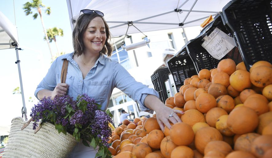 """This April 10, 2019 photo shows Gaby Dalkin shopping for oranges at Santa Monica Downtown Farmers Market in Santa Monica, Calif. Dalkin, the chef behind the popular Website and social media accounts, """"What's Gaby Cooking,"""" is forging her own path. Every Monday she posts a live demo to Instagram as she cooks dinner which has become appointment viewing for some fans. Her husband films it and reads questions from viewers as she's cooking. (AP Photo/Chris Pizzello)"""