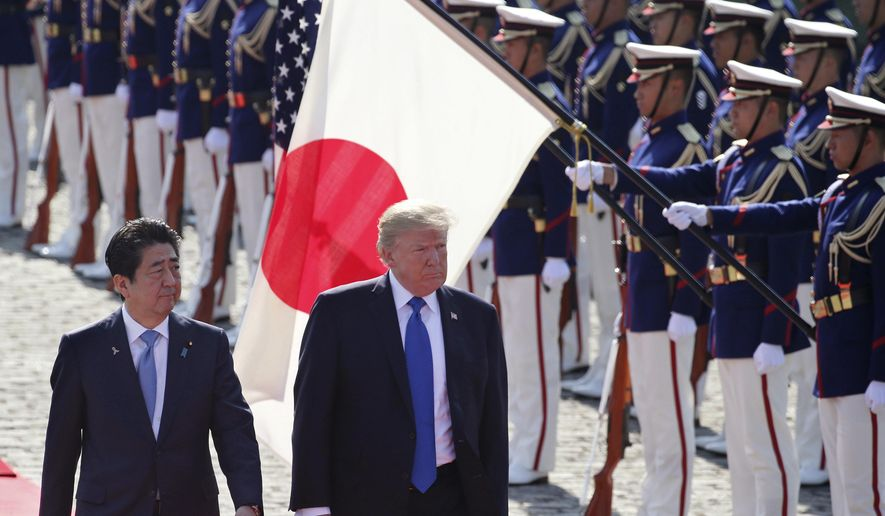 In this Nov. 6, 2017, file photo, U.S. President Donald Trump, second from left, reviews an honor guard during a welcome ceremony, escorted by Japanese Prime Minister Shinzo Abe at Akasaka Palace in Tokyo. Trump's Japan visit starting on Saturday, May 25, 2019, is to focus on personal ties with Abe rather than substantive results on trade, security or North Korea. (AP Photo/Koji Sasahara, Pool, File) **FILE**