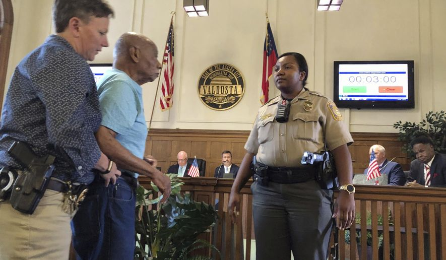 In this Thursday, May 23, 2019 photo, Police escort civil rights activist Floyd Rose out of a city council meeting at city hall, in Valdosta, Ga. Rose was pressing city officials to rename Forrest Street for the nation's first black president. He says the street was named in 1883 for Confederate Gen. Nathan Bedford Forrest, an early leader of the Ku Klux Klan. Valdosta Police Chief Leslie Manahan said Rose wasn't charged. (Thomas Lynn/The Valdosta Daily Times via AP)