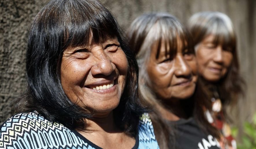 Maka indigenous leader-in-training Tsiweyenki, whose Spanish name is Gloria Elizeche, smiles with her sisters Cristina, center, and Estela as they cook in her backyard in Mariano Roque Alonso, Paraguay, Monday, April 29, 2019. Following the death of Tsiweyenki's husband, who was chief of the Maka, his widow has been chosen as one of the first female leaders of an entire ethnic group. (AP Photo/Jorge Saenz)