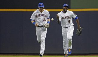 Milwaukee Brewers' Lorenzo Cain (6) smiles with Christian Yelich after making a catch at the wall on a ball hit by Philadelphia Phillies' Cesar Hernandez during the fifth inning of a baseball game Friday, May 24, 2019, in Milwaukee. (AP Photo/Aaron Gash)