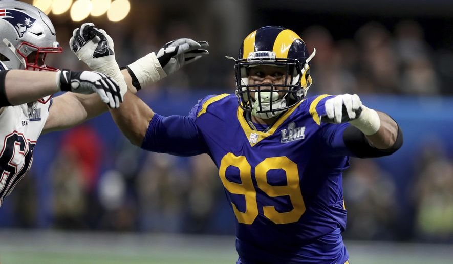 FILE - In this Feb. 3, 2019, file photo, Los Angeles Rams Aaron Donald (99) rushes against the New England Patriots during NFL Super Bowl 53 in Atlanta. Two-time reigning defensive player of the year Aaron Donald is always searching for out-of-the-box ways to improve his game. That's why the Rams defensive lineman trained with knives again this offseason. That's right, knives, of the plastic variety, of course, in order to improve his eye-hand coordination. His real driving force? That loss to the New England Patriots in the Super Bowl last February. (AP Photo/Gregory Payan, File)