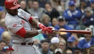 Cincinnati Reds' Yasiel Puig hits an RBI single against the Chicago Cubs during the fourth inning of a baseball game Friday, May 24, 2019, in Chicago. (AP Photo/Nam Y. Huh)
