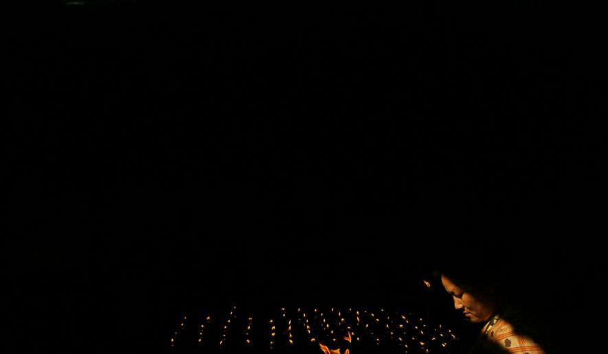 In this Saturday, May 18, 2019, file photo, a Nepalese Buddhist woman lights a butter lamp during Buddha Jayanti, or Buddha Purnima, festival in Kathmandu, Nepal. The festival marks the triple events of Gautam Buddha's life: his birth, his enlightenment and his attaining a state of Nirvana that frees believers from the circle of death and rebirth. (AP Photo/Niranjan Shrestha, File)