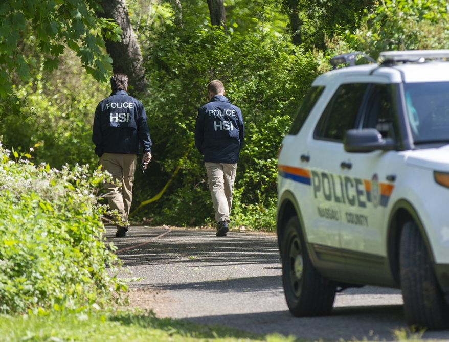 Nassau Police with federal partners conduct an investigation at the Massapequa preserve on Saturday, May 25, 2019 at the Massapequa Preserve in Massapequa, N.Y. after a body was found in a shallow grave the day before. The body has not been identified, but police say the victim is one of 11 people killed by MS-13 gang members in 2016. (Howard Schnapp/Newsday via AP)