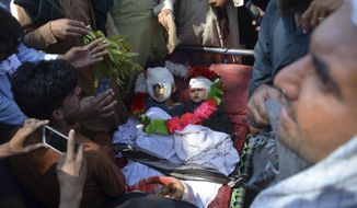 Afghan people stand over bodies of civilians during a protest in Nangarhar province east of Kabul, Afghanistan, Saturday, May 25, 2019. Afghan officials say at least six civilians, including a woman and two children, have been mistakenly killed in an Afghan security forces raid against Taliban fighters in eastern Nangarhar province. (AP Photo/Mohammad Anwar Danishyar)