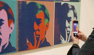 """In this photo taken Wednesday, May 15, 2019, a woman records one of a series of self portraits at the exhibition, """"Andy Warhol _ From A to B and Back Again"""", in San Francisco. A retrospective of Andy Warhol's work on display at the San Francisco Museum of Modern Art captures his use of artwork to give his subjects personas the way people do now using social media. (AP Photo/Eric Risberg) ** FILE **"""
