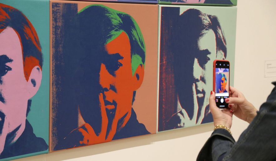 """In this photo taken Wednesday, May 15, 2019, a woman records one of a series of self portraits at the exhibition, """"Andy Warhol _ From A to B and Back Again"""", in San Francisco. A retrospective of Andy Warhol's work on display at the San Francisco Museum of Modern Art captures his use of artwork to give his subjects personas the way people do now using social media.   (AP Photo/Eric Risberg)"""