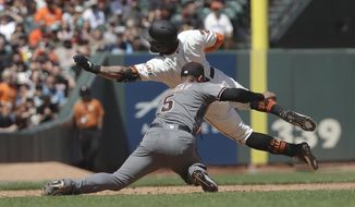 San Francisco Giants' Kevin Pillar, top, is tagged out by Arizona Diamondbacks third baseman Eduardo Escobar (5) while trying to reach third after doubling during the sixth inning of a baseball game in San Francisco, Saturday, May 25, 2019. (AP Photo/Jeff Chiu)