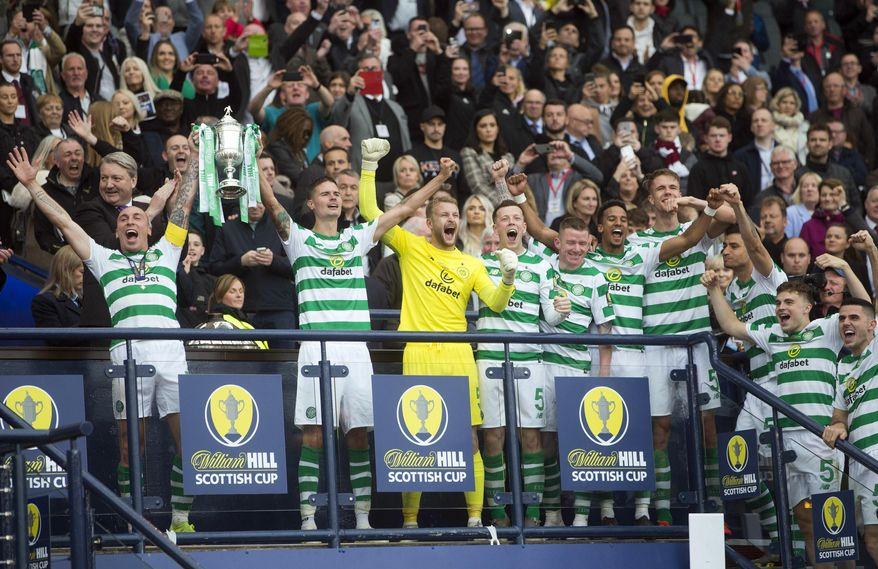 Celtic's Scott Brown, left, and Mikael Lustig celebrate with the trophy after winning the Scottish Cup Final at Hampden Park, Glasgow, Scotland, Saturday, May 25, 2019. Celtic wrapped up a domestic treble for an unprecedented third straight season after beating Hearts 2-1 in the Scottish Cup Final on Saturday.Having already won the Scottish League Cup and league titles, Celtic rallied at Hampden Park with a brace from striker Odsonne Edouard. (Jeff Holmes/PA via AP)