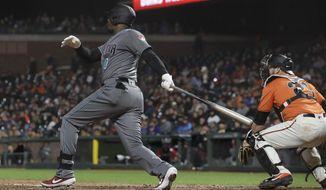 Arizona Diamondbacks' Adam Jones watches his three-run home run in front of San Francisco Giants catcher Stephen Vogt during the fifth inning of a baseball game in San Francisco, Friday, May 24, 2019. (AP Photo/Jeff Chiu)