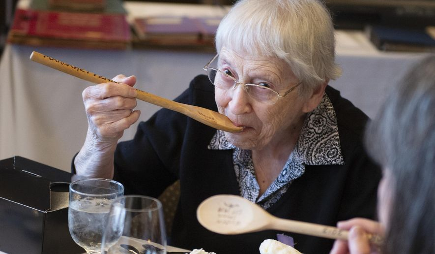 Margaret Penney, the person who has the longest membership of the Wooden Spoons, an all women's social club started by Louise Pound in 1919, takes a bite of ice cream with her wooden spoon during its final gathering on Tuesday, May 14, 2019, at US Bank. Penney became a member in 1969. It was tradition in the past to eat meals with the wooden spoons. Although the tradition stopped, Penney takes one bite using her spoon during the final gathering. (Emily Haney/Lincoln Journal Star via AP)