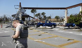 FILE- In this Oct. 11, 2018 file photo, a soldier stands guard at the damaged entrance to Tyndall Air Force Base in Panama City, Fla.,  in the aftermath of Hurricane Michael. (AP Photo/David Goldman, File)