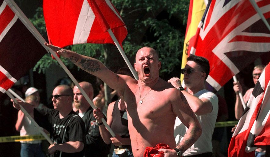 In this July 18, 1998, file photo, Karl Wolf raises his arm in a Nazi salute as he marches through the streets of Coeur d'Alene, Idaho, where scores of police in riot gear stood between parading white supremacists and protesters who jeered at the Aryan Nations marchers. Nearly two decades after the Aryan Nations compound was demolished in Idaho, far-right extremists are maintaining a presence in the Pacific Northwest. White nationalism has been on the rise across the U.S., but it has particular resonance along the Idaho-Washington border. (AP Photo/Elaine Thompson, File)