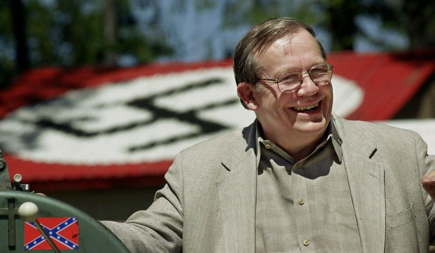 FILE - In this May 22, 2001, file photo, Norm Gissel smiles as he talks about the imminent dismantling of the former headquarters of the Aryan Nations in Hayden Lake, Idaho. Behind Gisel is a Nazi insignia painted atop the roof of the compound's cafeteria. Nearly two decades after the Aryan Nations compound was demolished in Idaho, far-right extremists are maintaining a presence in the Pacific Northwest. (AP Photo/Elaine Thompson, File)