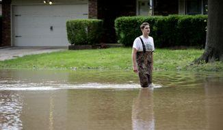 Grant Scepanski walks through his Indian Springs Estates neighborhood in Broken Arrow, Okla., as flood water from the Arkansas River rises Friday, May 24, 2019. (Mike Simons/Tulsa World via AP)