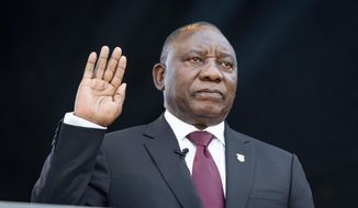 South African President Cyril Ramaphosa, right, takes the Oath of Office at the Loftus Versfeld Stadium in Pretoria, South Africa, Saturday, May 25, 2019. Ramaphosa has vowed to crack down on the corruption that contributed to the ruling ANC' s weakest election showing in a quarter-century. (Yeshiel Panchia/Pool Photo via AP)