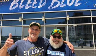 In this May 22, 2019 photo, longtime St. Louis Blues fans Stanley Jackson, left, and Steven Crow stand in front of the Enterprise Center in St. Louis, a day after the Blues defeated San Jose to earn a berth in the Stanley Cup Finals. The two friends, in their 50s, are life-long fans of the franchise that has never won a Stanley Cup. (AP Photo by Jim Salter)