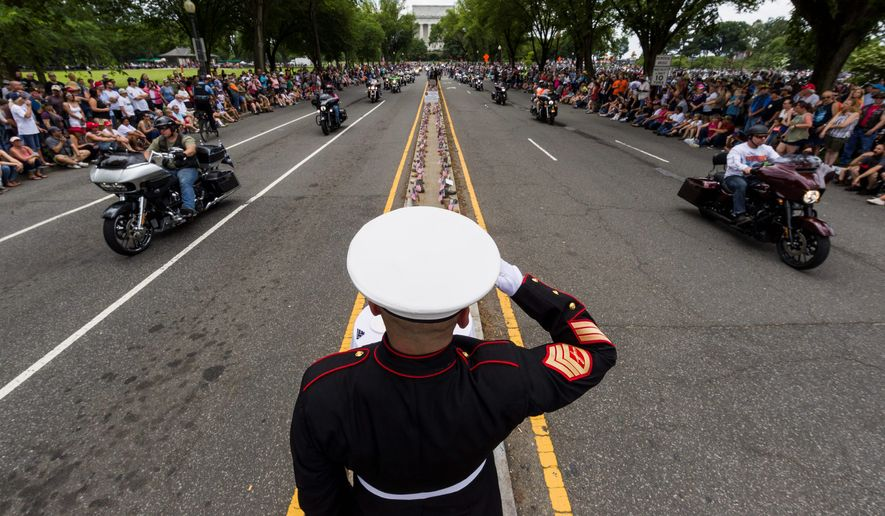 U.S. Marine Corps Staff Sgt. Tim Chambers salutes as motorcyclists ride in the 32nd Operation Rolling Thunder rally on Sunday in the District. The event honors prisoners of war and those killed in action. (Associated Press)