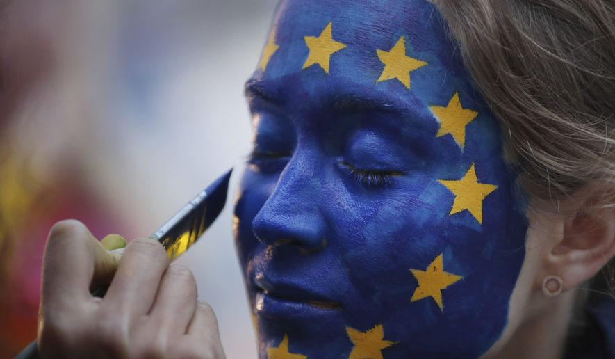 A woman has her face painted as the EU flag during a festival outside the European Parliament in Brussels, Sunday, May 26, 2019. (AP Photo/Francisco Seco)