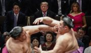 President Donald Trump attends the Tokyo Grand Sumo Tournament with Japanese Prime Minister Shinzo Abe at Ryogoku Kokugikan Stadium, Sunday, May 26, 2019, in Tokyo. First lady Melania Trump is at top right. (AP Photo/Evan Vucci)