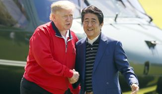 U.S. President Donald Trump, left, is welcomed by Japanese Prime Minister Shinzo Abe upon arrival for playing a round of golf at Mobara Country Club in Mobara, south of Tokyo, Sunday, May 26, 2019. (Kimimasa Mayama/Pool Photo via AP)
