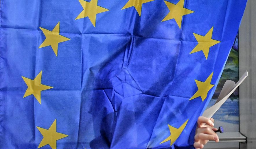 A woman exits a voting cabin with curtains depicting the European Union in Baleni, Romania, Sunday, May 26, 2019. The ruling Social Democratic Party (PSD) suffered a major blow in the European Parliament elections according to the country's only exit poll. (AP Photo/Andreea Alexandru)