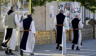 Monks from the Saint Sixtus Trappist Abbey walk by election campaign posters as they walk to a polling station in Westvleteren, Belgium, Sunday, May 26, 2019. Belgium, which has one of the oldest compulsory voting systems, goes to the polls Sunday to vote on the regional, federal and European level. (AP Photo/Olivier Matthys)