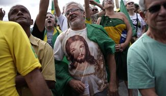 A man wearing a Jesus T-shirt shouts slogans during a rally in favor of Brazil's President Jair Bolsonaro on Copacabana beach in Rio de Janeiro, Brazil, Sunday, May 26, 2019. The pro-Bolsonaro rally follows anti-government protests against cuts in the education budget as the president also battles an uncooperative Congress, a family corruption scandal and falling approval ratings after five months in office. (AP Photo/Silvia Izquierdo)