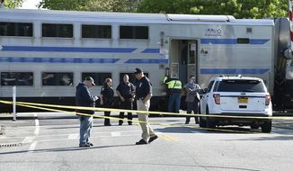 """Authorities gather at the scene of a Long Island Rail Road passenger train derailment in Southampton, N.Y., Saturday, May 25, 2019. The LIRR tweeted that the derailment followed a """"slow-speed impact"""" between a passenger train and a work train at around 4 a.m. Saturday. No injuries were reported. Train service to the east end of Long Island is suspended for the first day of Memorial Day weekend after the early morning derailment. (John Roca/Newsday via AP)"""