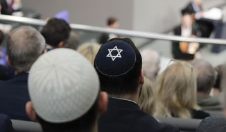 In this Thursday, Jan. 31, 2019, file photo, two men wearing skullcaps as they listen to the speech of Israeli Historian Saul Friedlaender, during a remembrance event of the parliament Bundestag to commemorate the victims of the Holocaust at the Reichstag building in Berlin. Israeli President Reuven Rivlin said Sunday he is shocked by a statement by Felix Klein, the government's anti-Semitism commissioner, that he wouldn't advise Jews to wear skullcaps in parts of the country for their safety. (AP Photo/Markus Schreiber)