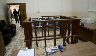 FILE - in this Thursday, April 26, 2018 file photo, the defendant's cage is in the center of an empty courtroom at Nineveh Criminal Court, one of two counterterrorism courts in Iraq where suspected Islamic State militants and their associates are tried, in Tel Keif, Iraq. A Baghdad court sentenced to death three French citizens Sunday for being members of the Islamic State group, an Iraqi judicial official said. The official said the three were among 12 French citizens handed over to Iraq in January by the U.S.-backed Syrian Democratic Forces. Then SDF has handed over to Iraq hundreds of suspected IS members in recent months. (AP Photo/Maya Alleruzzo, File)