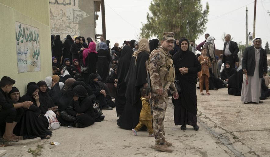 FILE - in this Thursday, April 26, 2018 file photo, relatives wait outside Nineveh Criminal Court, one of two counterterrorism courts in Iraq where suspected Islamic State militants and their associates are tried, in Tel Keif, Iraq. A Baghdad court sentenced to death three French citizens Sunday for being members of the Islamic State group, an Iraqi judicial official said. The official said the three were among 12 French citizens handed over to Iraq in January by the U.S.-backed Syrian Democratic Forces. Then SDF has handed over to Iraq hundreds of suspected IS members in recent months. (AP Photo/Maya Alleruzzo, File)
